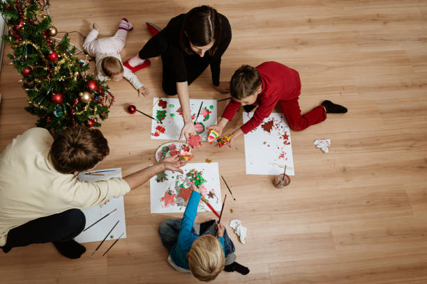 Family of five making holiday decorations stock photo
