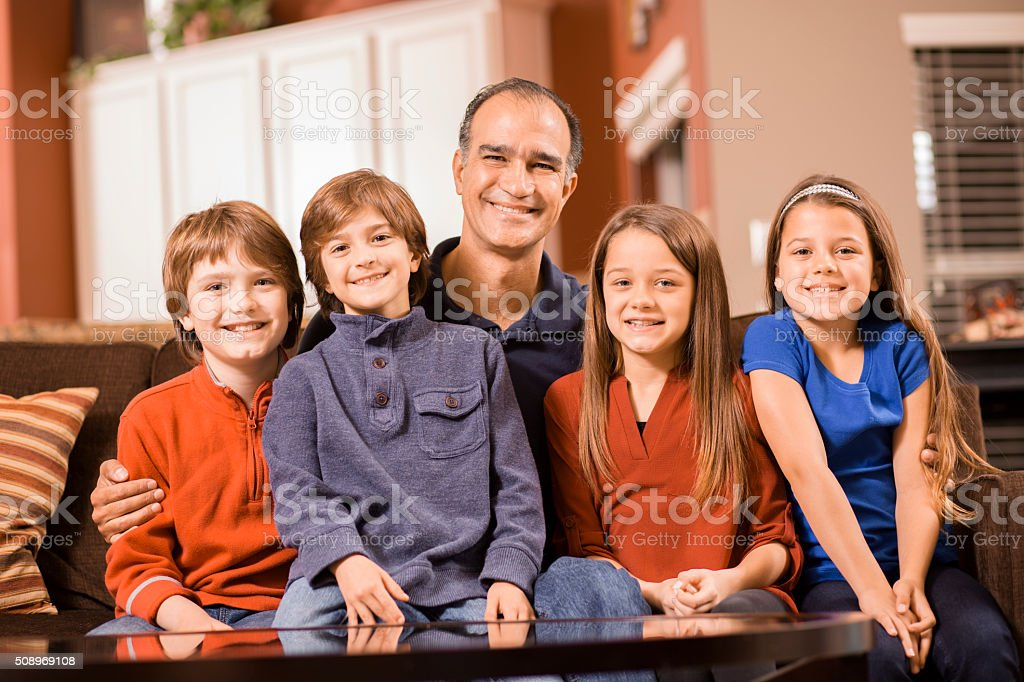 Family of five poses together at home.  Mixed races. stock photo