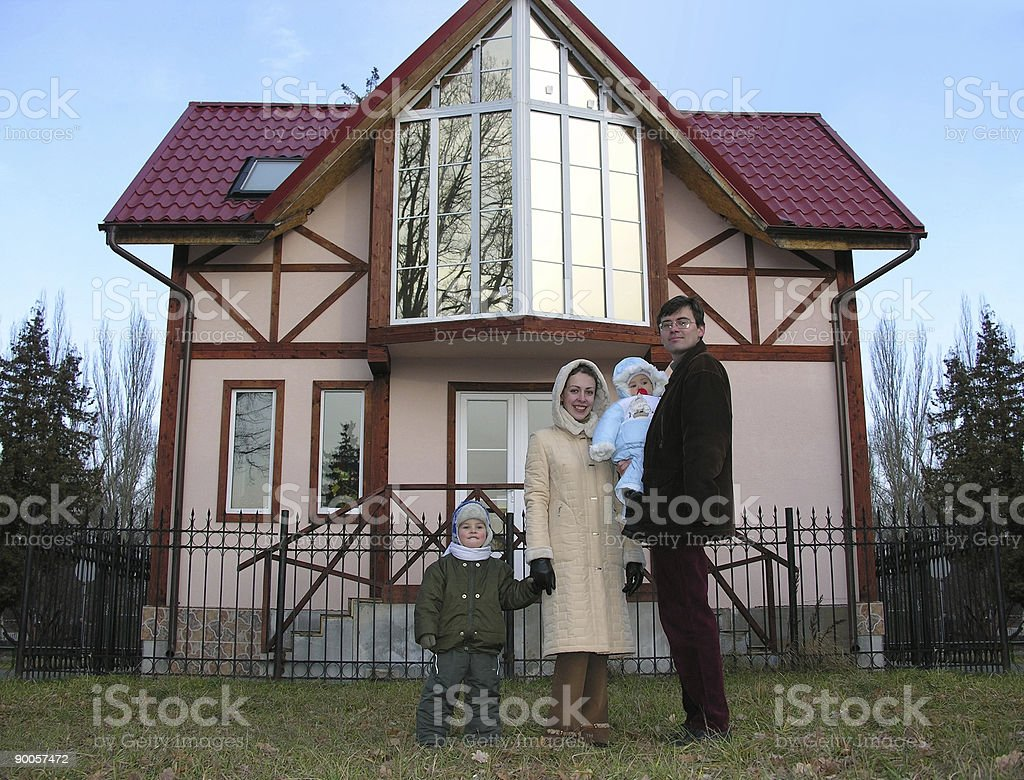family of four and home stock photo