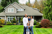 Portrait of a happy young African American family standing in front of their American suburban home.