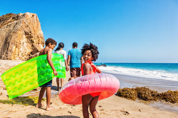 family of four at the beach - family vacation stock photos and pictures