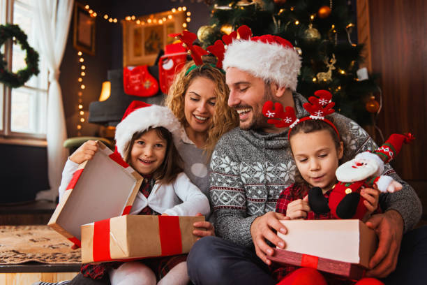 Family of four celebrating Christmas, exchanging presents stock photo