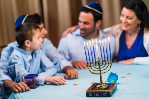 family of four celebrating hanukkah - hanukkah stock pictures, royalty-free photos & images