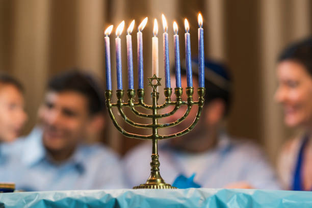 Family of four celebrating hanukkah A jewish family of four sitting around a table talking, out of focus in the background. The younger boy is 7 years old and his brother is 13. The focus is on the menorah in the foreground judaism stock pictures, royalty-free photos & images