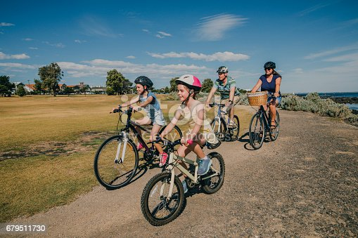 Family of four cycling in the park on a sunny day in Australia.
