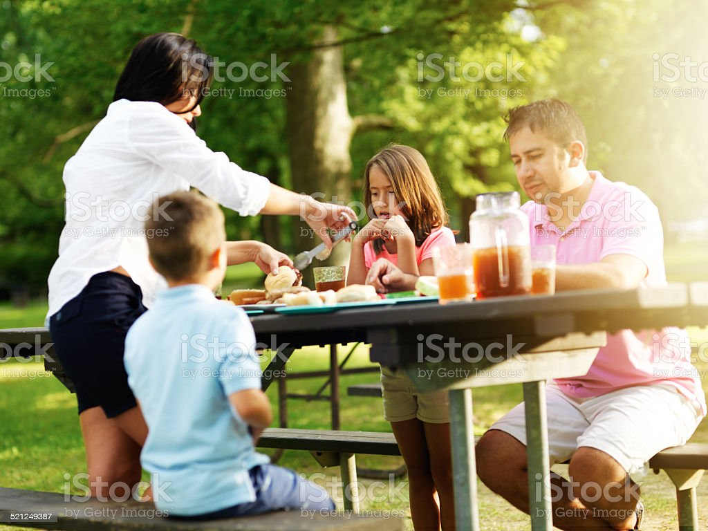 family of four eating at barbecue cookout stock photo