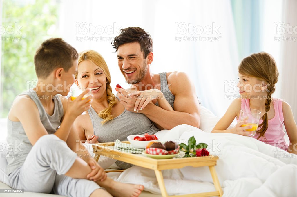 Family of four eating breakfast in bed foto royalty-free
