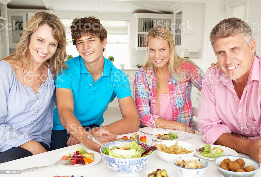Family of four enjoying a full meal at home royalty-free stock photo
