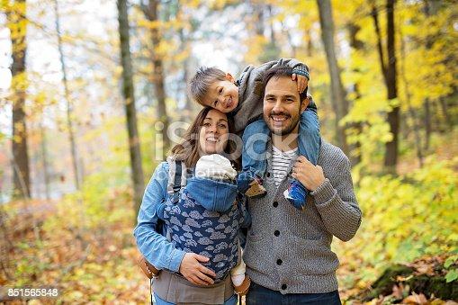 istock Family of four enjoying golden leaves in autumn park 851565848