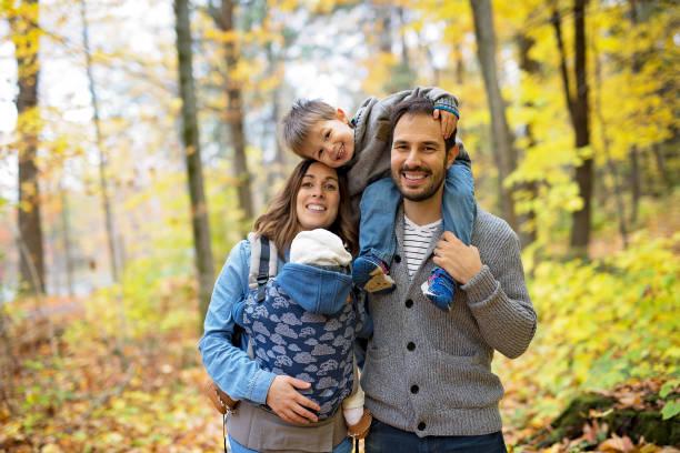 Family of four enjoying golden leaves in autumn park stock photo