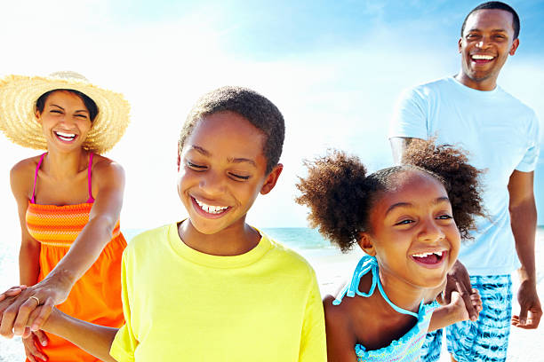 Family of four enjoying summer vacation in the beach stock photo