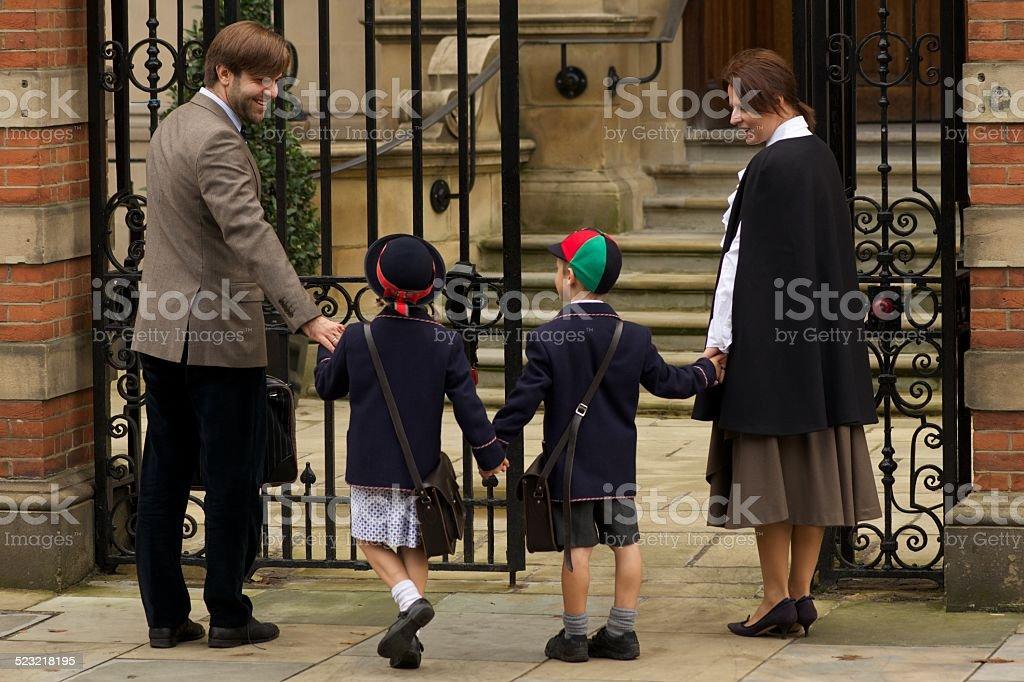 Family of four entering old school gates stock photo