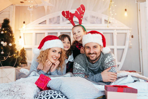 Family of four having fun for Christmas on the bed stock photo