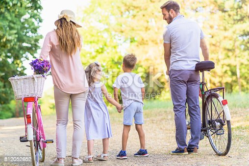 658444674istockphoto Family of four having fun with bikes in nature 812052652