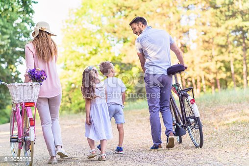 658444674istockphoto Family of four having fun with bikes in nature 812055228