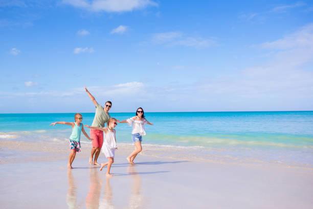 Vierköpfige Familie auf Urlaub am Strand laufen und Spaß haben – Foto
