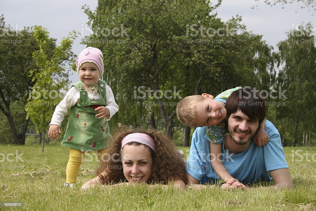family of four on grass stock photo