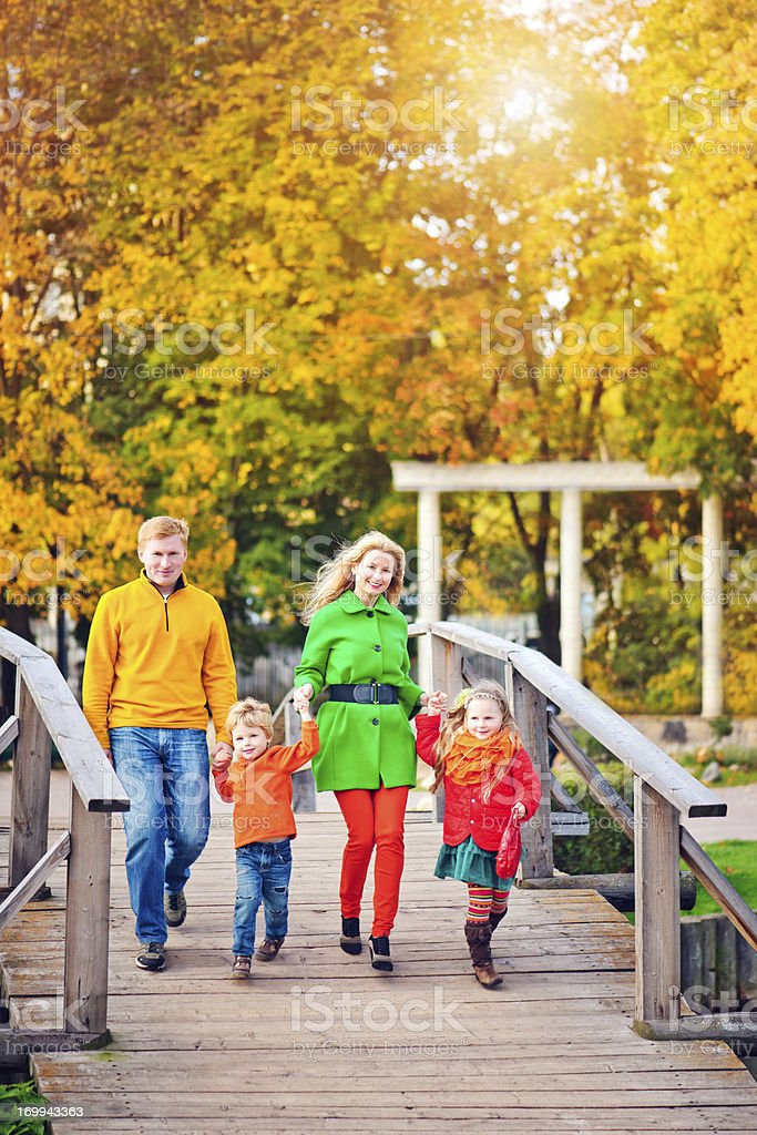 Family of four outdoors in autumn park royalty-free stock photo