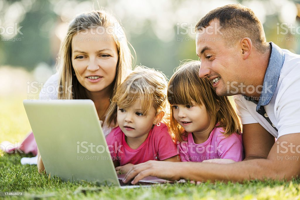 Family of four people lying in park and using laptop. royalty-free stock photo