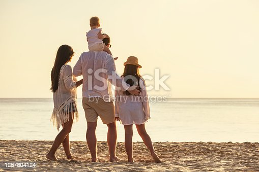Family of four unrecognizable people are standing with small daughters at sunset sea beach