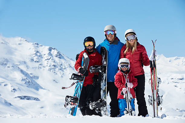 Family of four posing for photo with ski gear Family On Ski Holiday In Mountains Smiling To Camera. ski holiday stock pictures, royalty-free photos & images