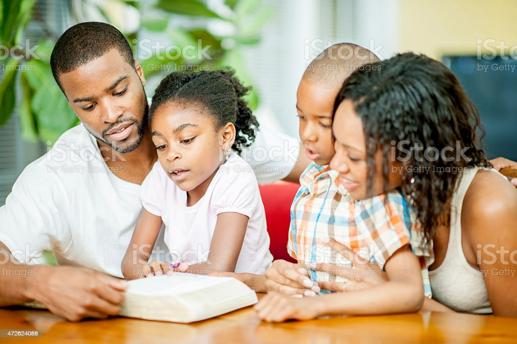 Family of Four Reading the Bible Together stock photo