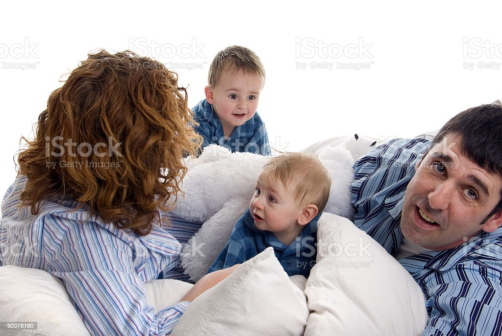 Family of four relaxes in bed royalty-free stock photo