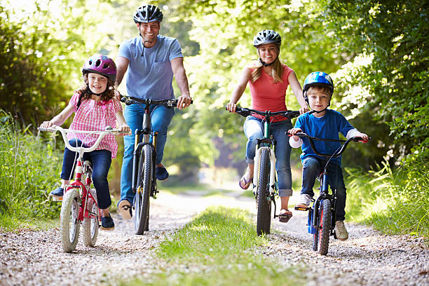 Family of four riding bikes on gravel road Family On Cycle Ride In Countryside Smiling At Camera leisure equipment stock pictures, royalty-free photos & images