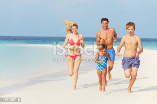 88688880 istock photo A family of four running on the white sands of a beach 167299716