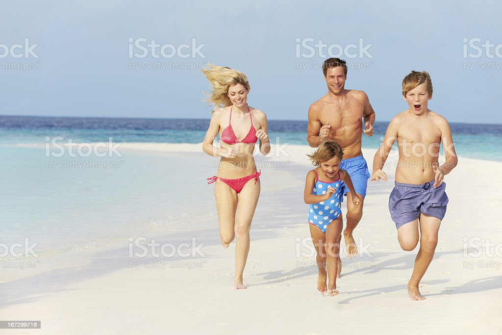 A family of four running on the white sands of a beach stock photo