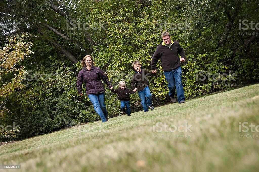 Family Of Four Running Outdoors royalty-free stock photo