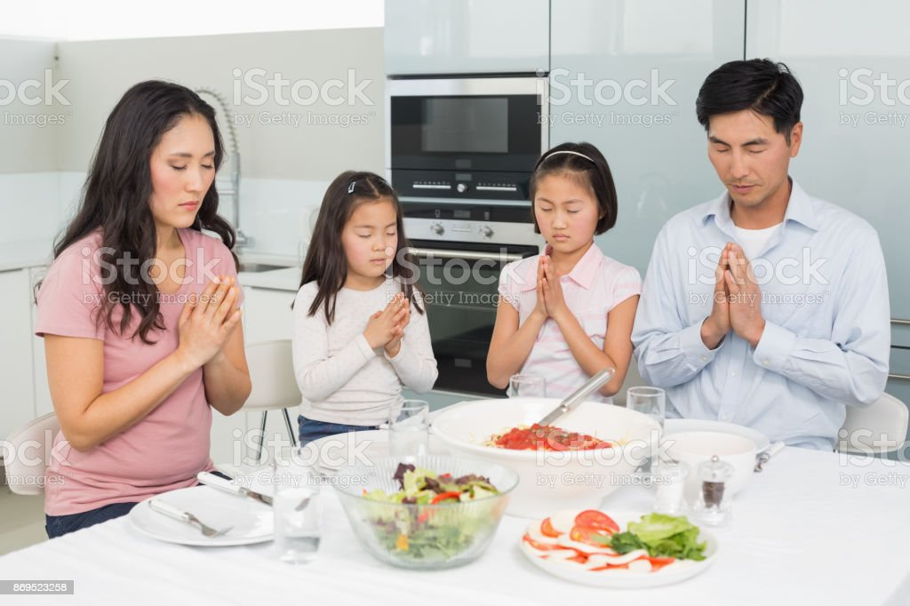 Family of four saying grace before meal in kitchen stock photo