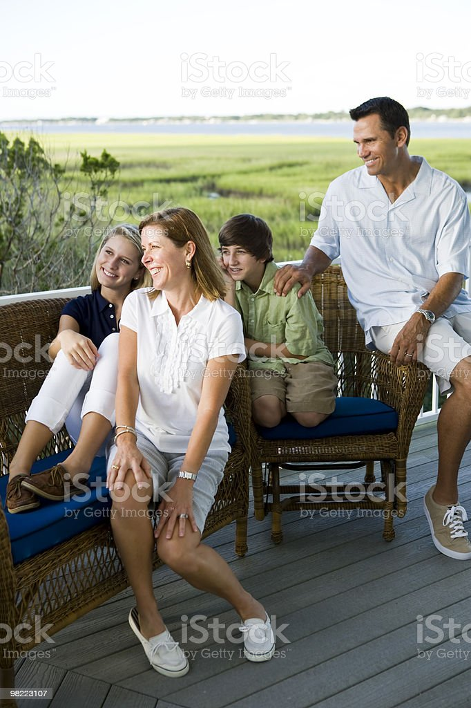 Family of four sitting together outdoors on terrace royalty-free stock photo