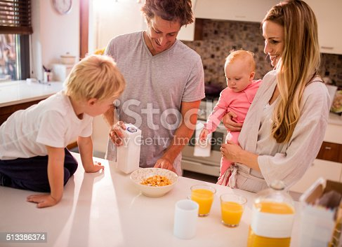 istock Family of Four Standing and Having Breakfast in Kitchen 513386374