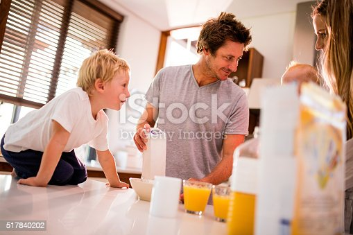 istock Family of Four Standing and Having Breakfast in Kitchen 517840202