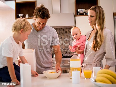 istock Family of Four Standing and Having Breakfast in Kitchen 518285552