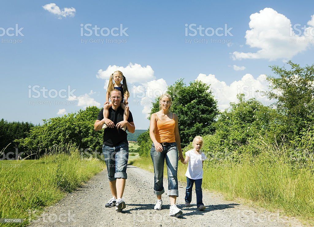 Family of four walking down a gravel road in the sunshine  royalty-free stock photo