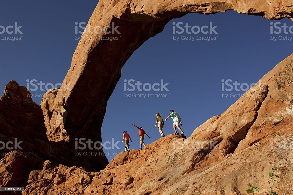 Family of Four Walking On  Rocks In Arches National Park stock photo