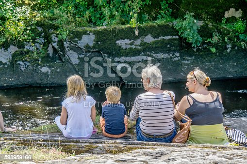 Cenarth, UK - July 31, 2016: Family of four watching sport sitting on riverbank at Cenarth in West Wales