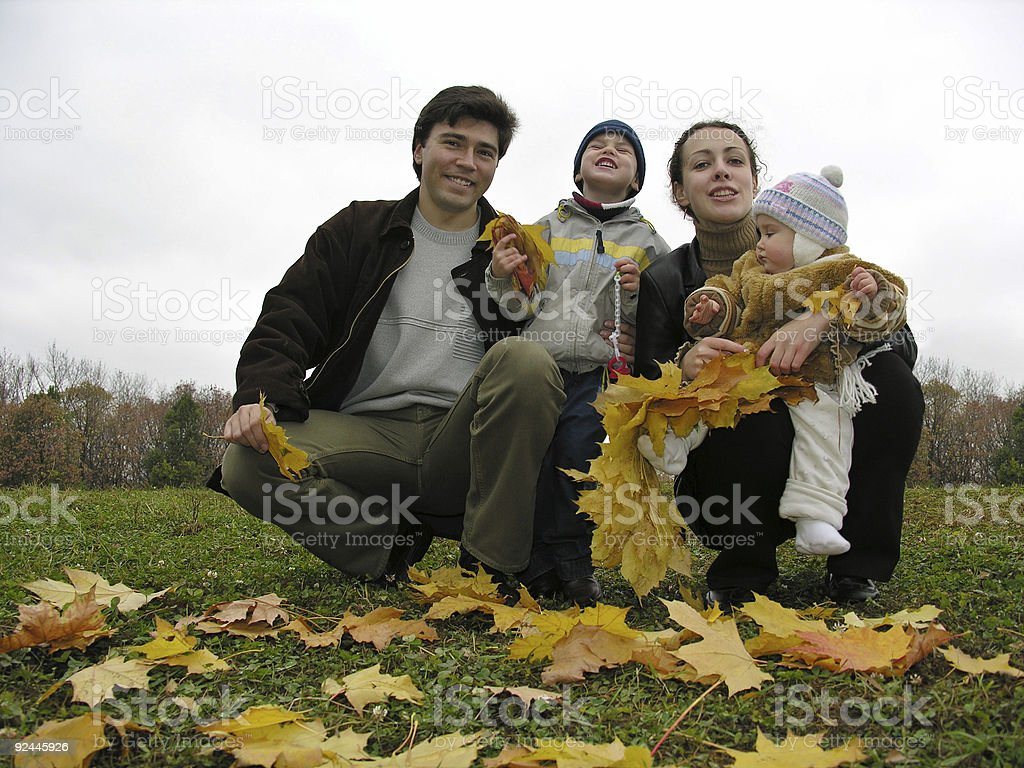 family of four with autumn leaves royalty-free stock photo
