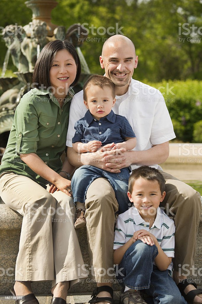 Family of Four with Two Boys Portrait by Park Fountain royalty-free stock photo