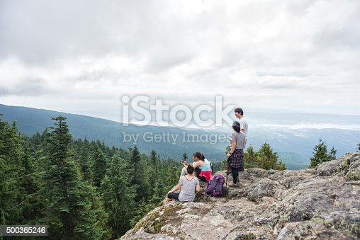 903015102 istock photo Family of Hikers Rest and Enjoy View on Wilderness Mountaintop 500365246