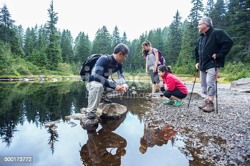 1051098428istockphoto Family of Hikers Resting at Shoreline of Alpine Lake, Canada 500173772