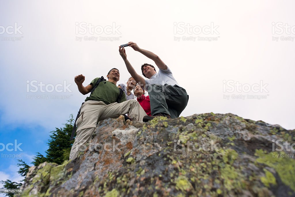 Family of Hikers Taking Selfie with Smartphone on Mountain Top stock photo