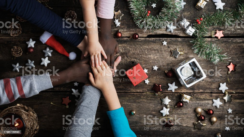 Family of mixed races stacking their hands in Christmas setting Top view of a family of mixed races stacking their hands in the middle of Christmas setting of  ornaments and candles. African Ethnicity Stock Photo