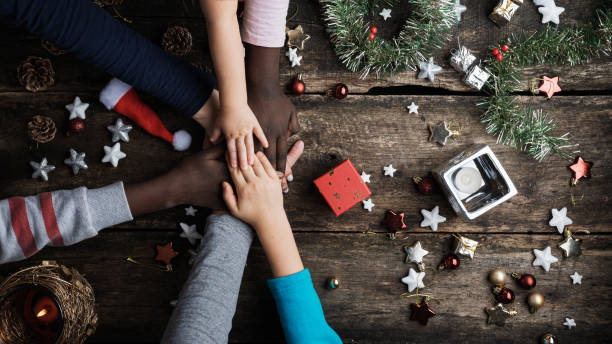 Family of mixed races stacking their hands in Christmas setting stock photo