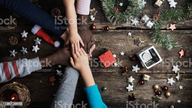 Family Of Mixed Races Stacking Their Hands In Christmas Setting Stock Photo - Download Image Now