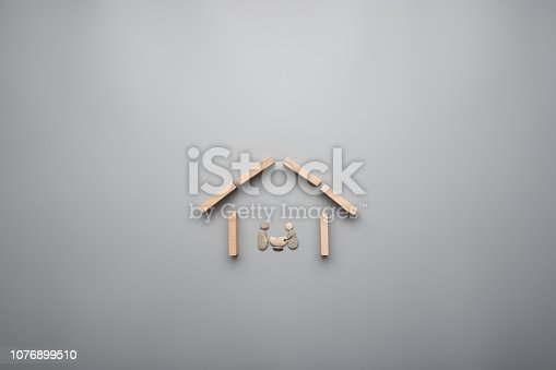 958039576istockphoto Family of parents and baby made of pebbles in a house made of wooden pegs 1076899510