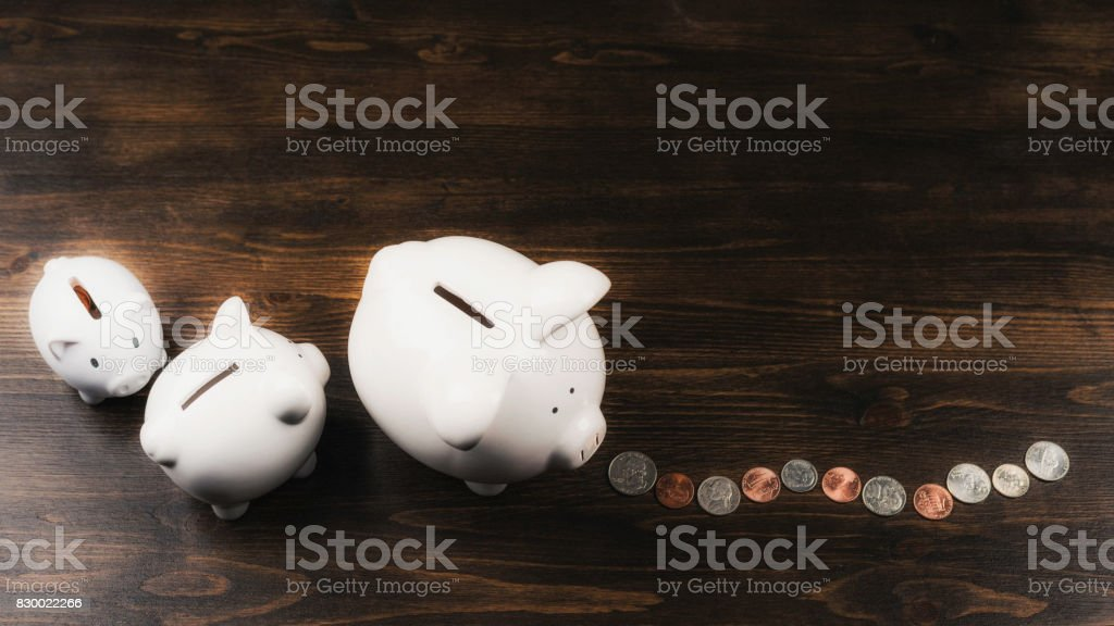 Family of piggy banks following a money trail stock photo