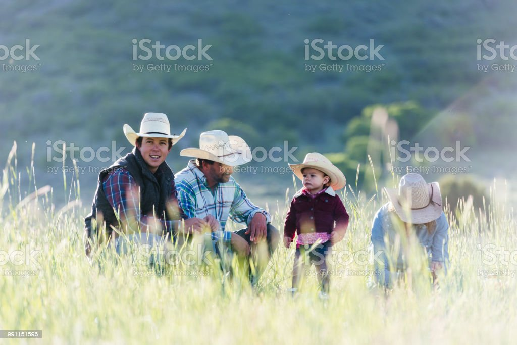 Family of ranchers enjoying the early morning outdoors young man looking to camera stock photo